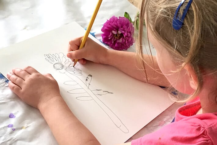 Child drawing flower for nature inspired art activity
