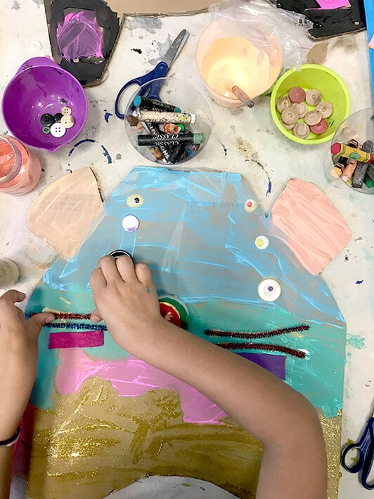 Child using paint, buttons, oil pastels, yarn, scissors and glue to create Miró inspired animal masks for kids