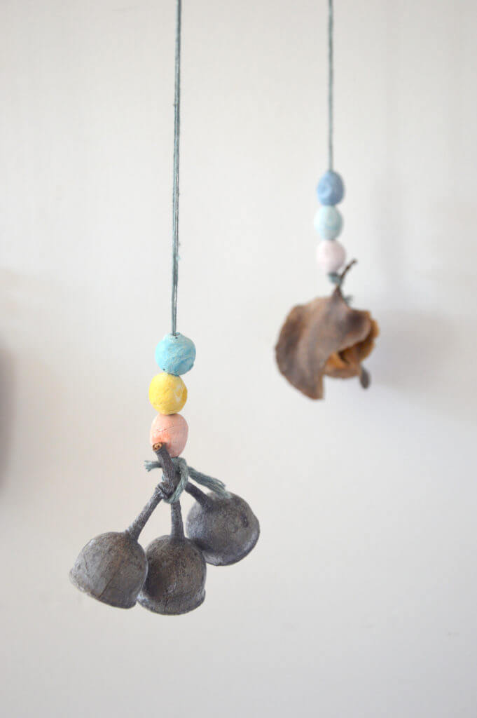 Hanging colored clay beads with nature object attached for nature mobile