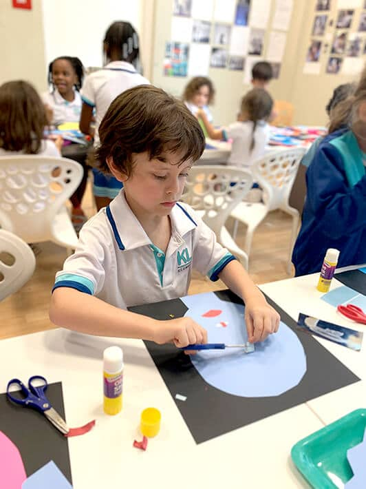 Boy cutting and glueing paper shapes for Picasso inspired self portrait collage