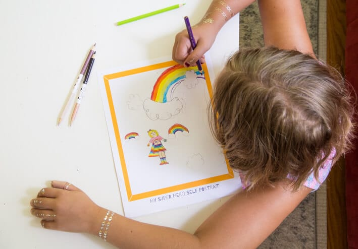 Child drawing her superhero self portrait with rainbow powers
