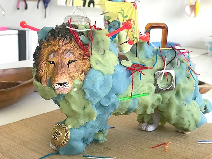 Lion figurine decorated with playdough and other items