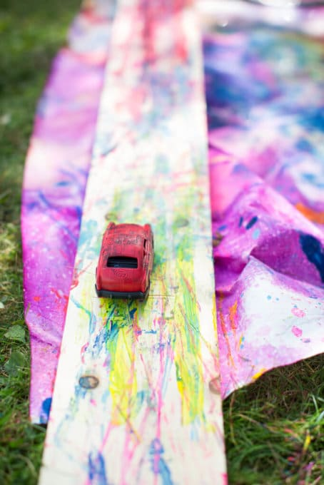 A red car on a painted wood ramp