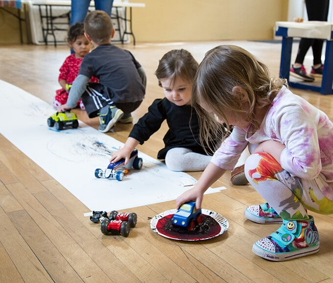 Kids roll cars in paint to create painted tracks on a roll of paper