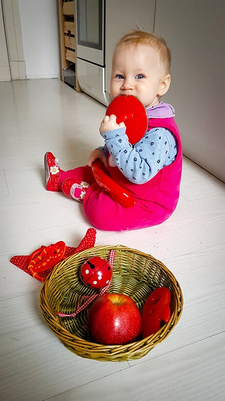 A sensory basket of red items with baby