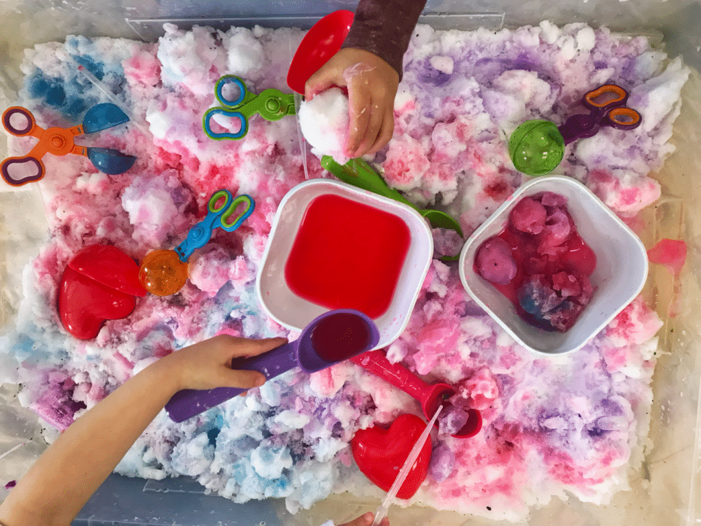 Valentine themed sensory bin with snow, scoopers & liquid watercolors