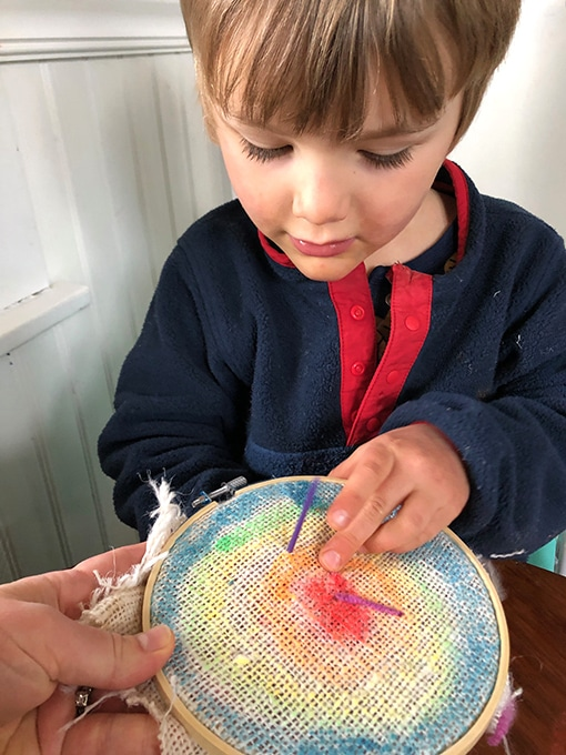Boy stitching on embroidery hoop with burlap