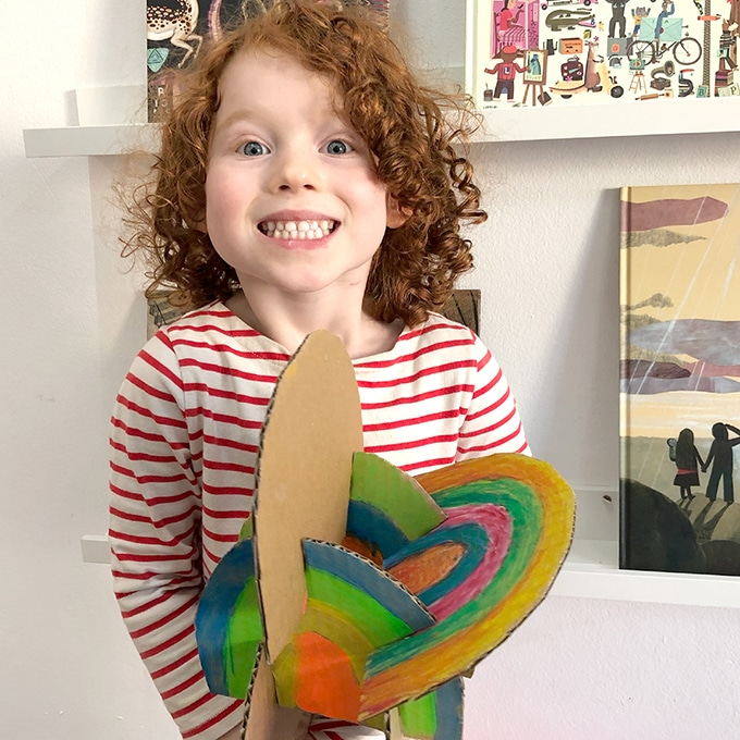 Child-holding-rainbow-cardboard-sculpture
