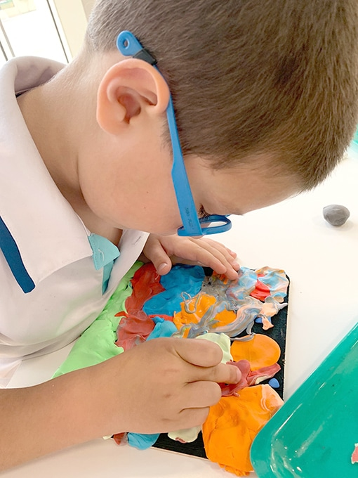 Child pressing colored air dry clay onto wooden board